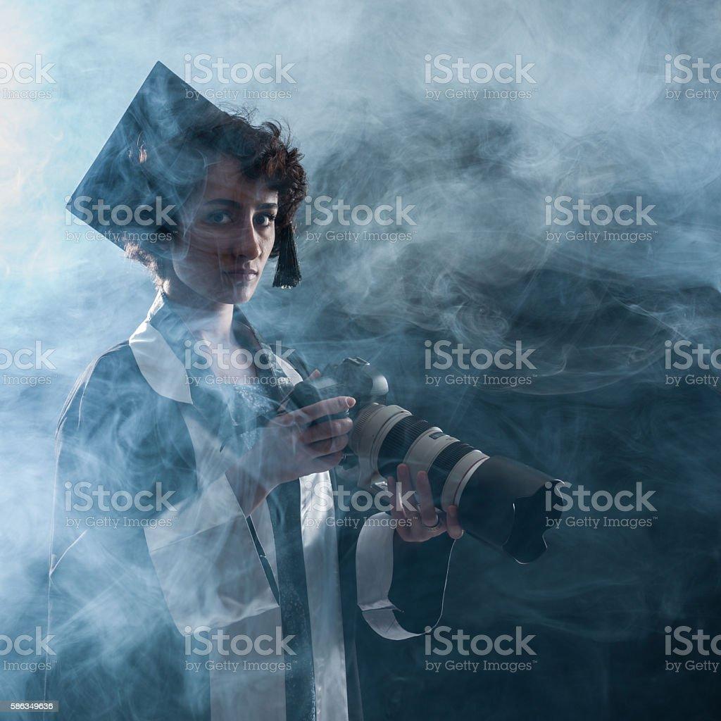 Newly Graduate Female Journalist Holding Camera In Fog stock photo