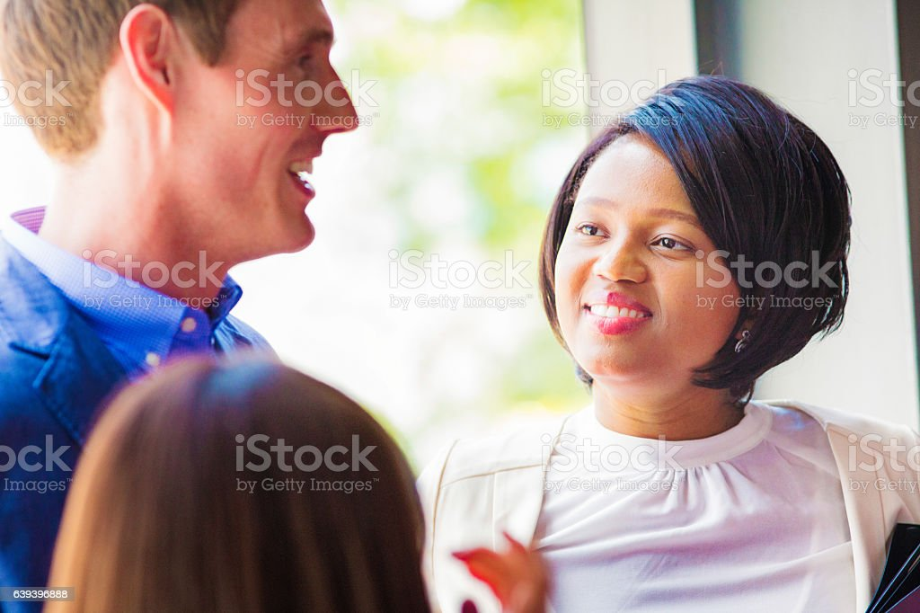 Newly hired female office worker smiles listening to instructions stock photo