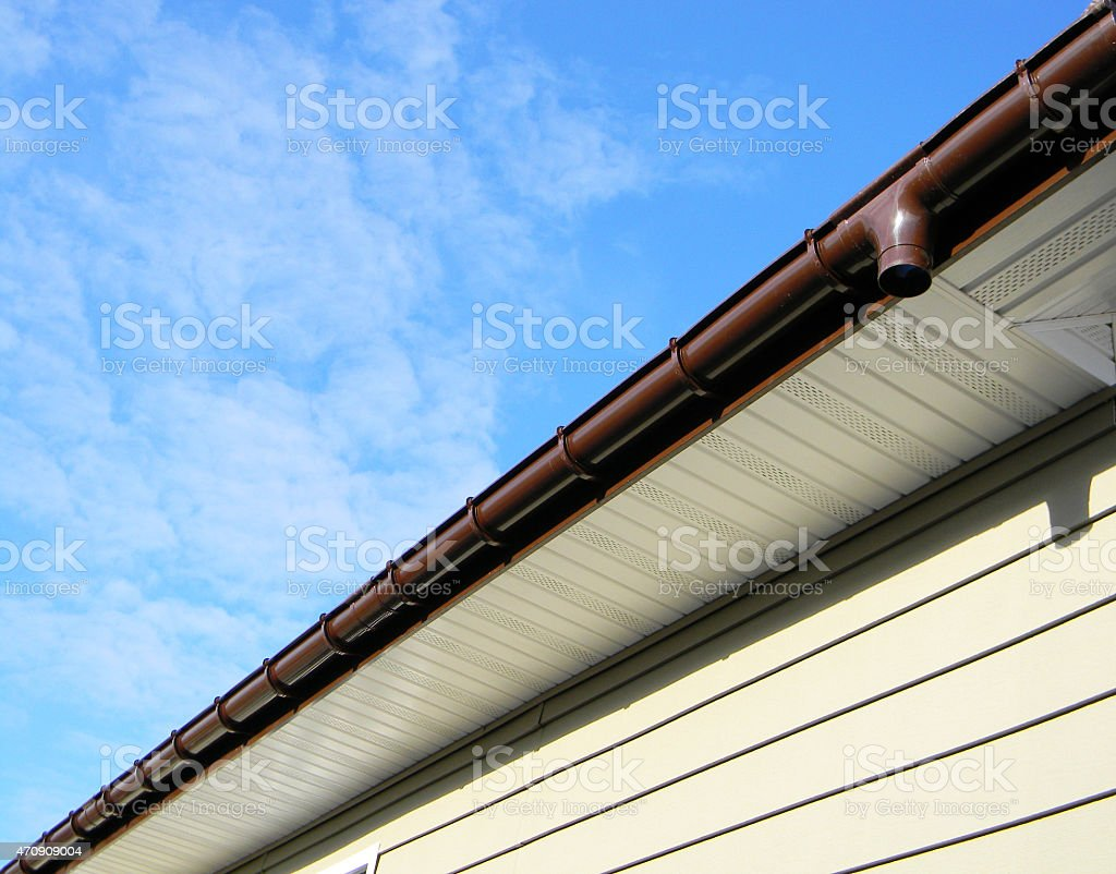Newly installed modern rain gutter against blue cloudy sky stock photo