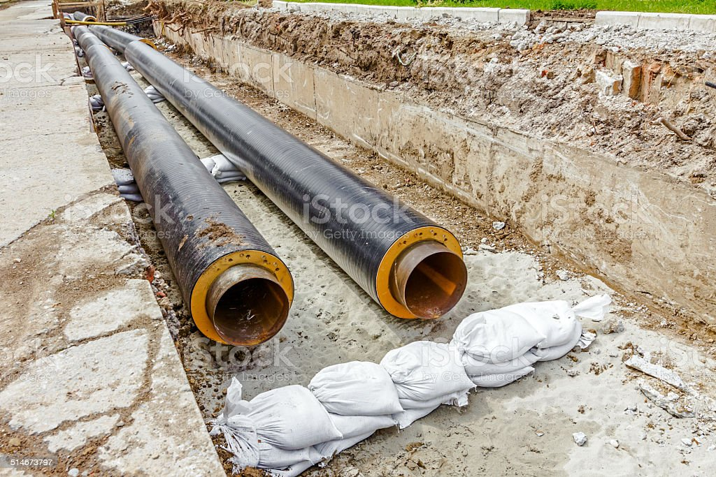 Newly laid pipe in a fresh trench. Unfinished pipeline stock photo