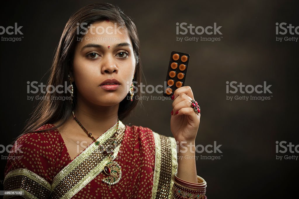 Newly married Hindu young woman holding sachet of medicine tablets. stock photo