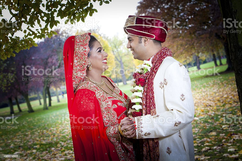 Newly married Indian couple embracing in the serene parkland stock photo