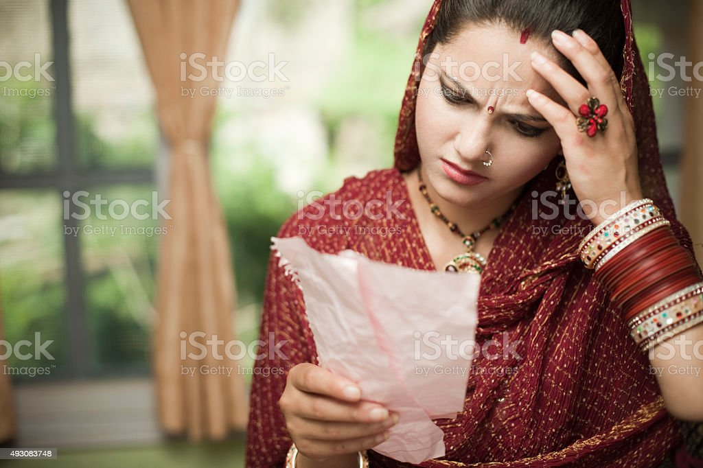 Newly married Indian woman reading torn paper by recombining them. stock photo