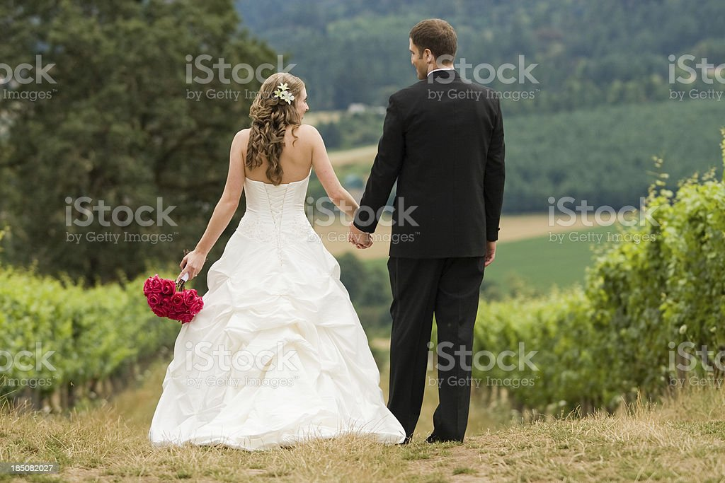 Newly Wed Couple Standing Walking on a Path Holding Hands stock photo