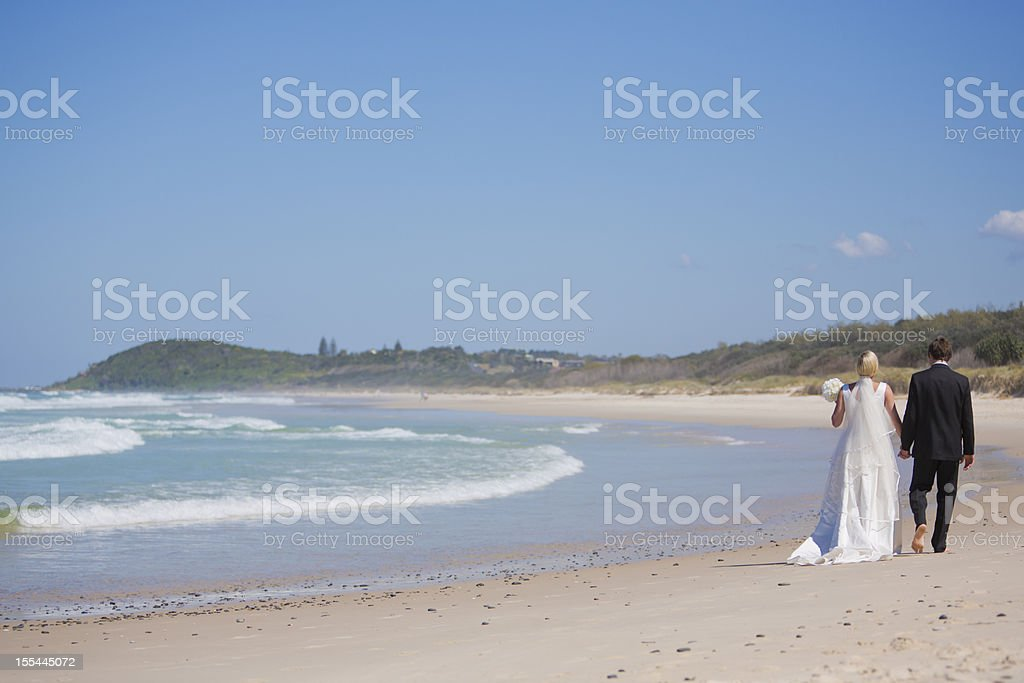Newly Wed Couple Walking on the Beach royalty-free stock photo