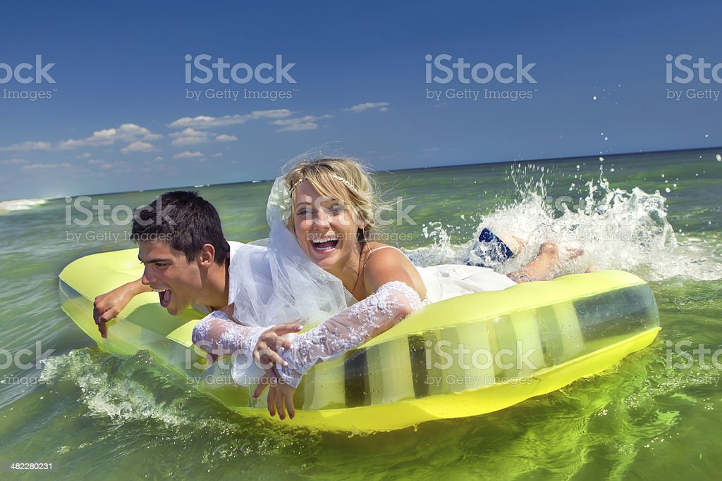 Newly-married couple enjoying on an inflatable mattress royalty-free stock photo