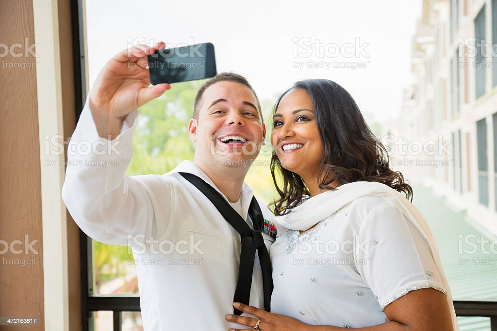 Newlywed American sailor shooting selfie with his exotic wife royalty-free stock photo