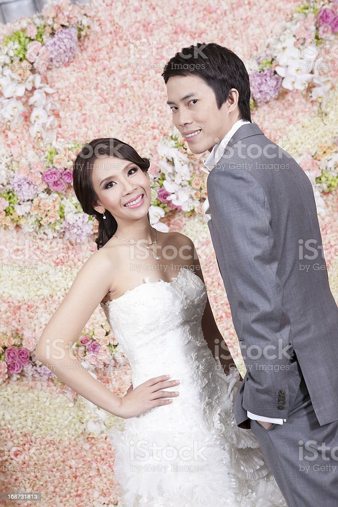 Newlywed bride and groom posing with flower decoration in backgr royalty-free stock photo