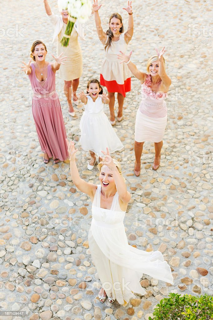 Newlywed Bride Throwing Flower Bouquet At Wedding Guests stock photo