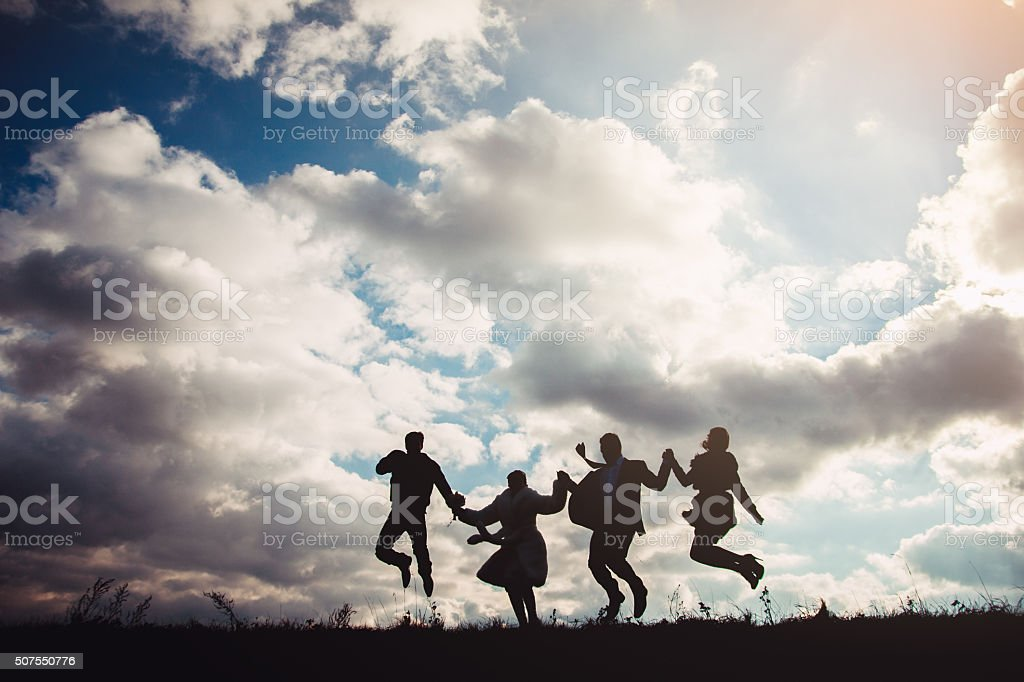Newlywed couple and their friends are jumping stock photo