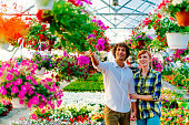 Newlywed couple buying flowers for home decoration