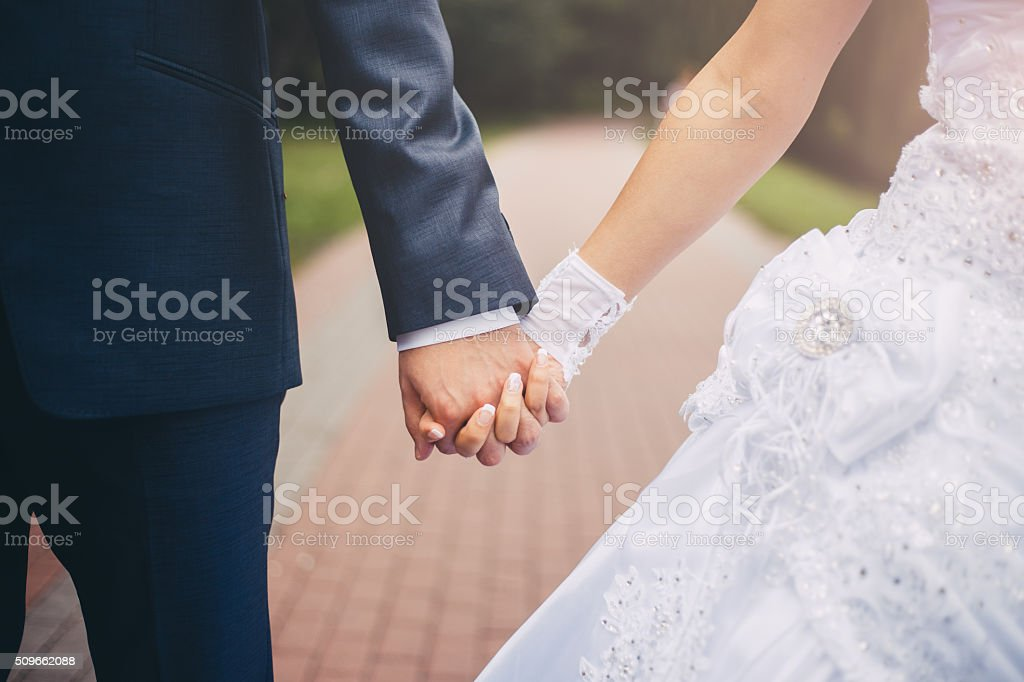 Newlywed couple holding hands stock photo