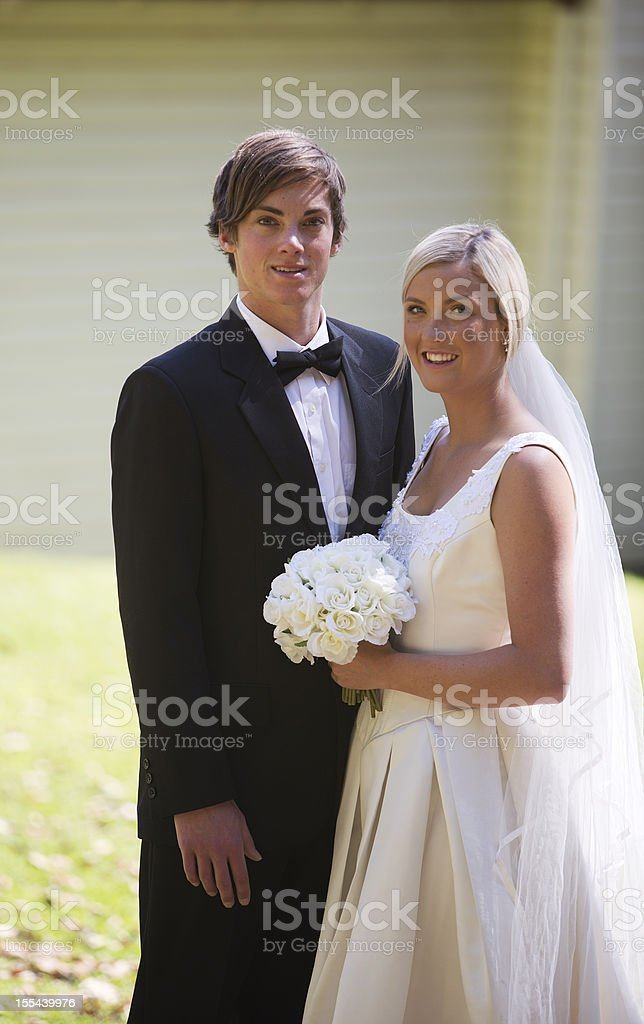 Newlywed Couple Hugging in Front of a Country Church royalty-free stock photo