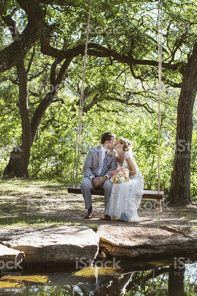 Newlywed Couple Kissing on a Swing royalty-free stock photo