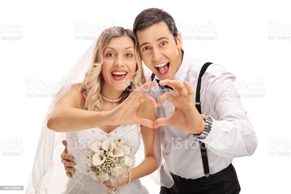 Newlywed couple making heart gesture stock photo