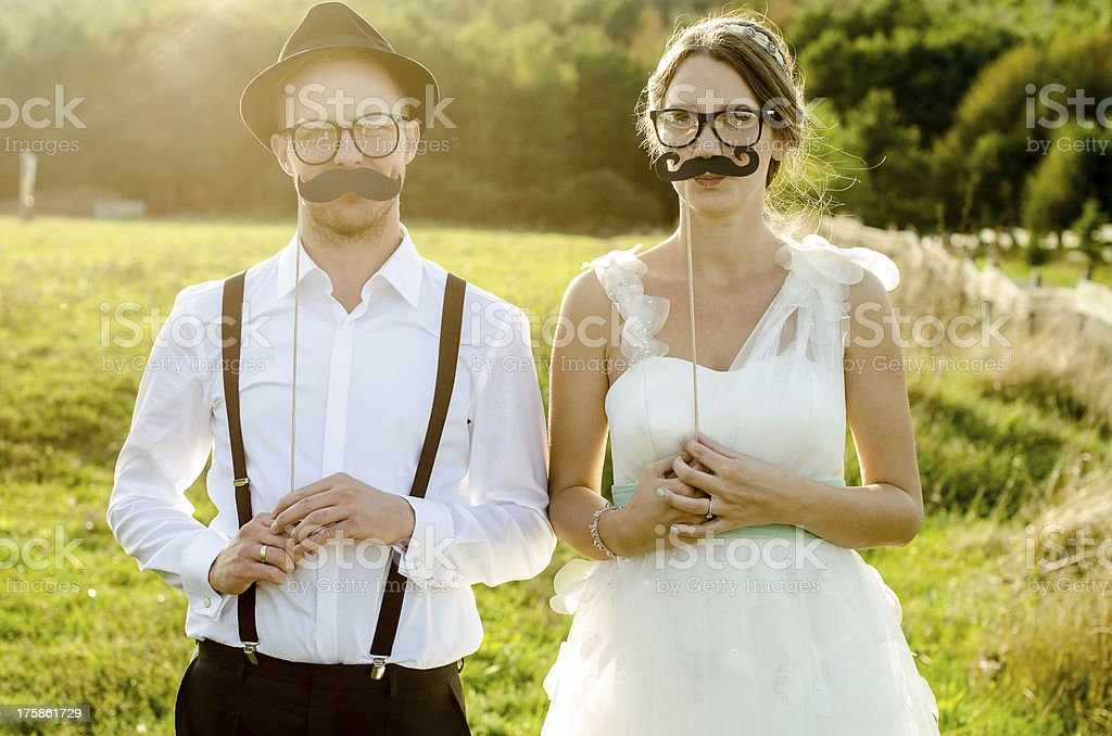 A newlywed couple poses with fake mustaches and glasses royalty-free stock photo