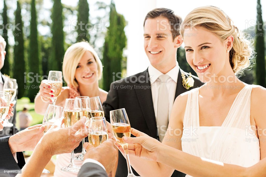 Newlywed Couple Toasting Champagne Flutes With Guests At Wedding stock photo