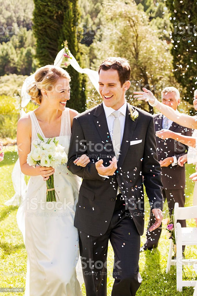 Newlywed Couple Walking While Guests Throwing Confetti On Them royalty-free stock photo