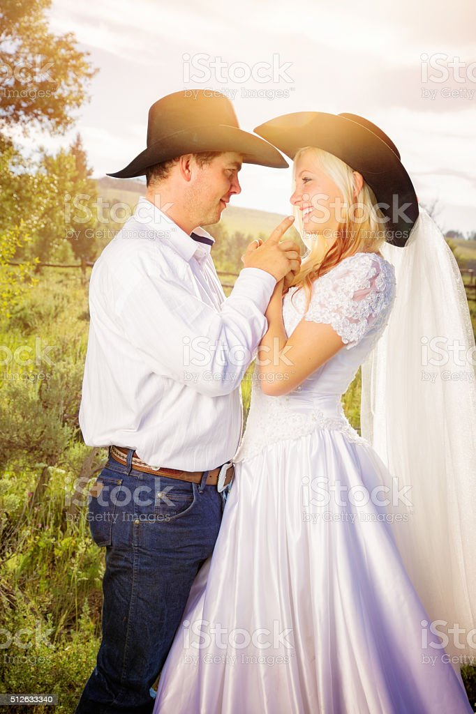 Newlywed cowboy couple portrait outdoors with lens flare stock photo