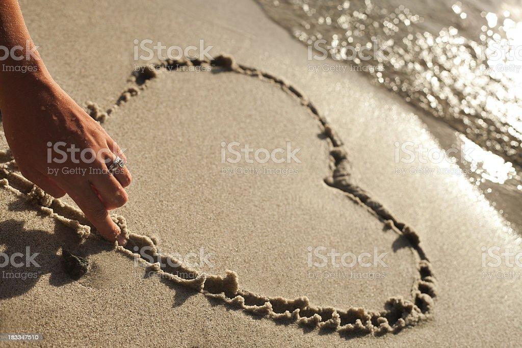 Newlywed draws  heart shape in the sand on honeymoon. royalty-free stock photo