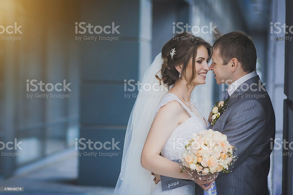 newlyweds against a blue modern building stock photo