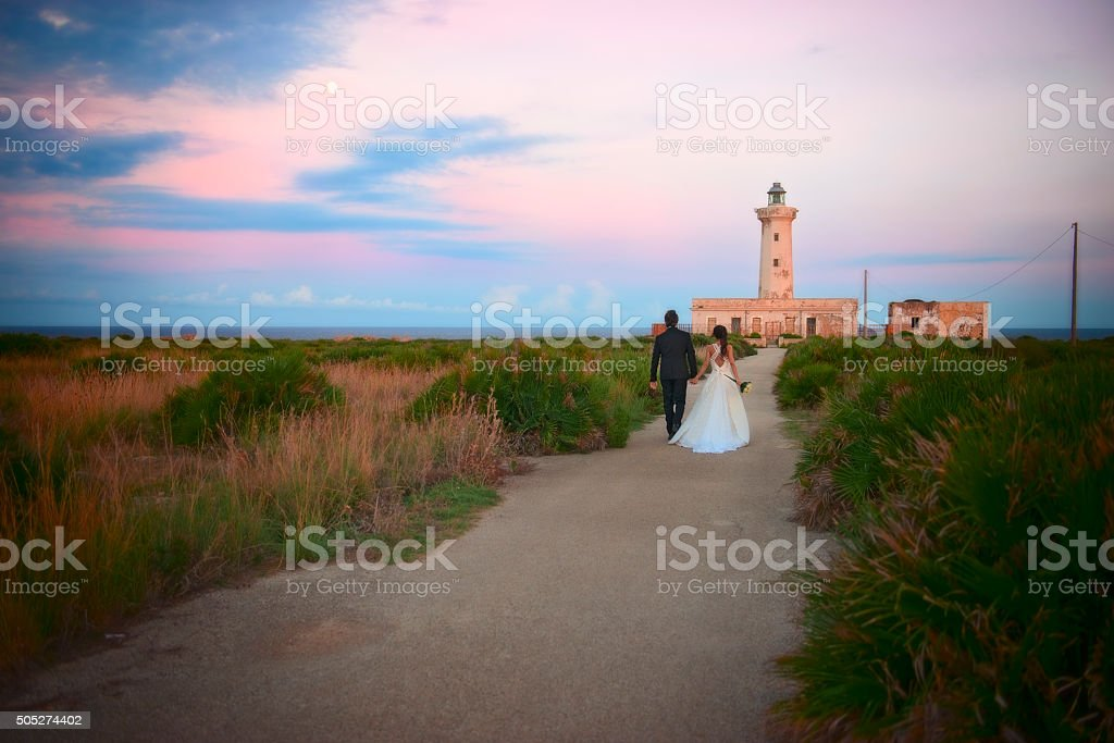 Newlyweds at Plemmirio Lighthouse, in Sicily. stock photo