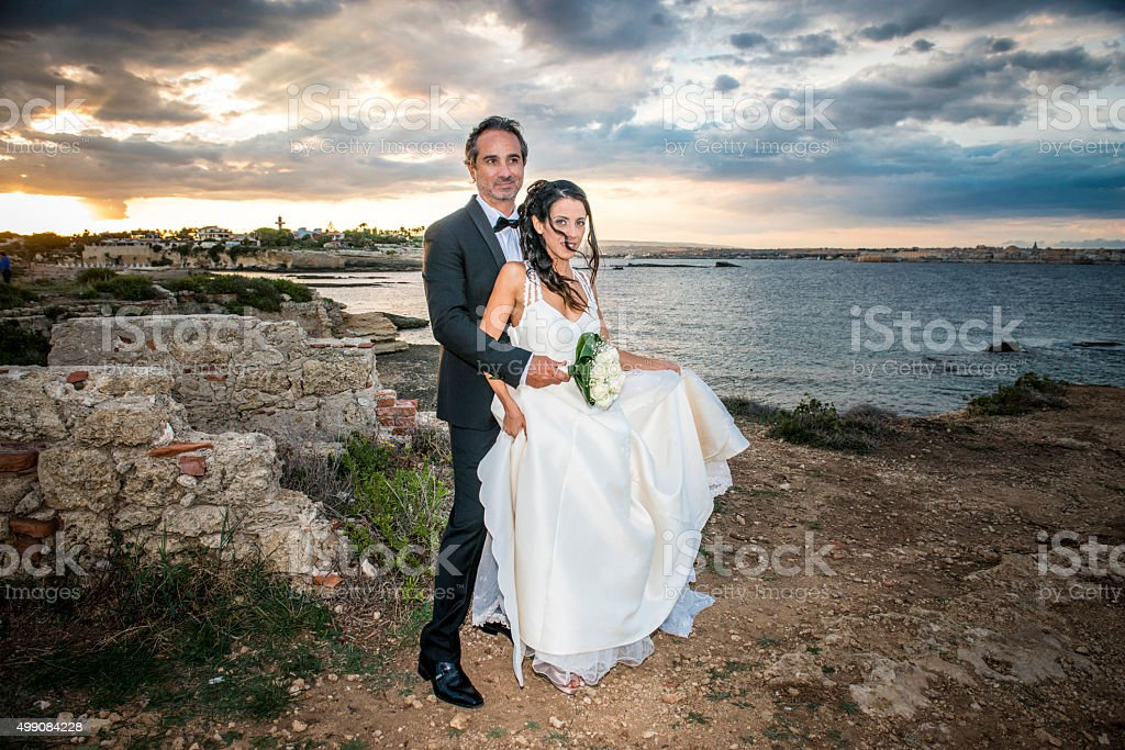 Newlyweds at Plemmirio park, in Sicily. stock photo