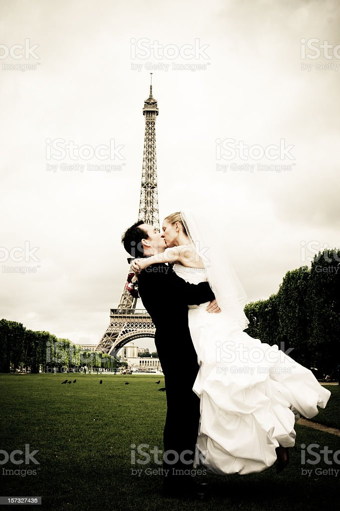 Newlyweds celebrate first kiss on the lawn of Eiffel Tower stock photo