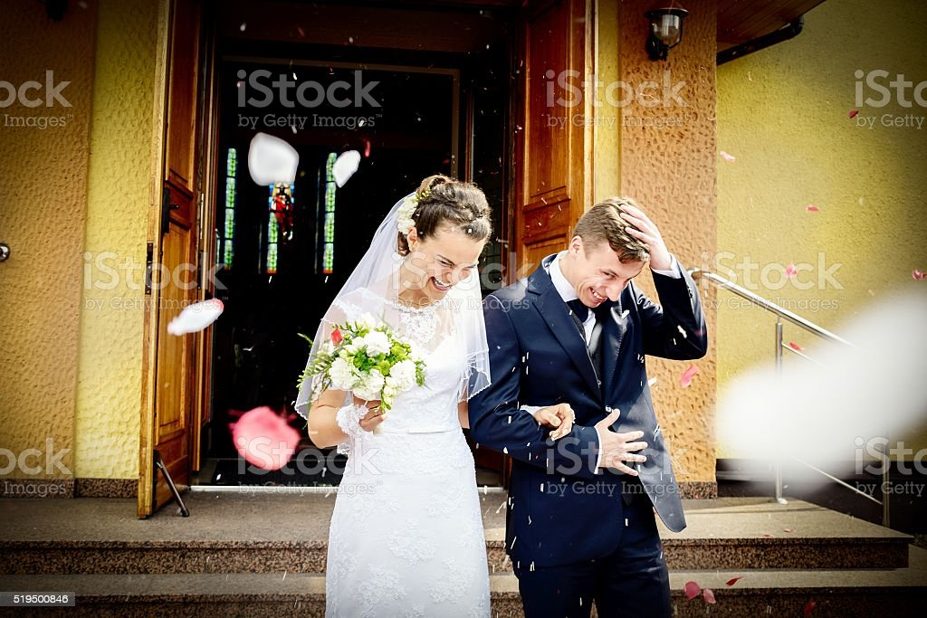 Newlyweds coming out of the church after wedding ceremony. stock photo