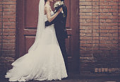 Newlyweds embracing next to red brick wall.