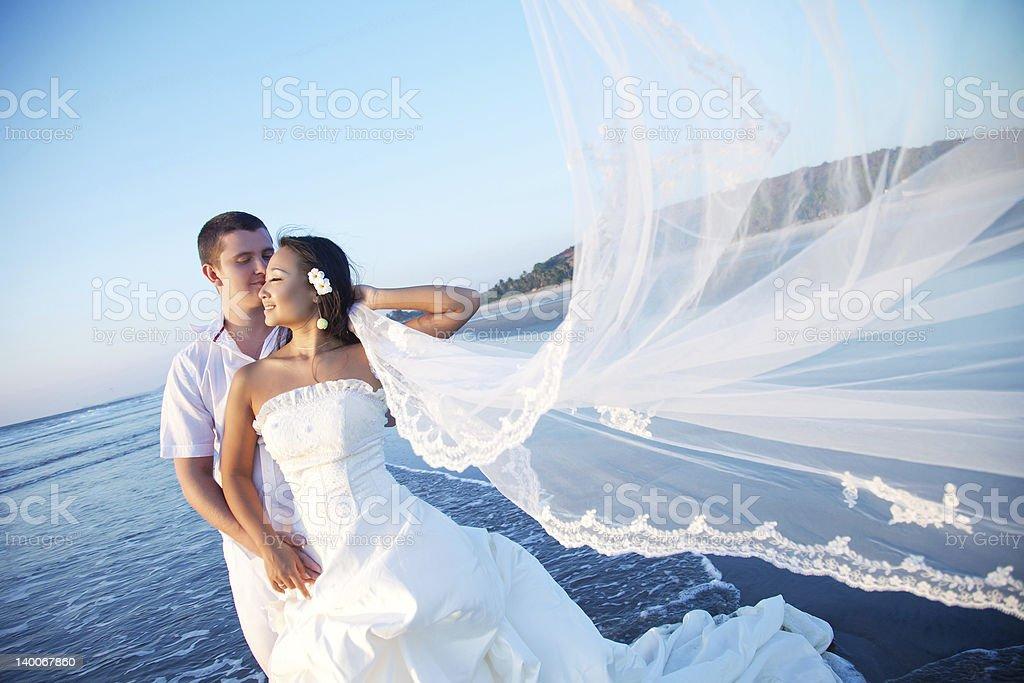 Newlyweds on the beach at sunset stock photo