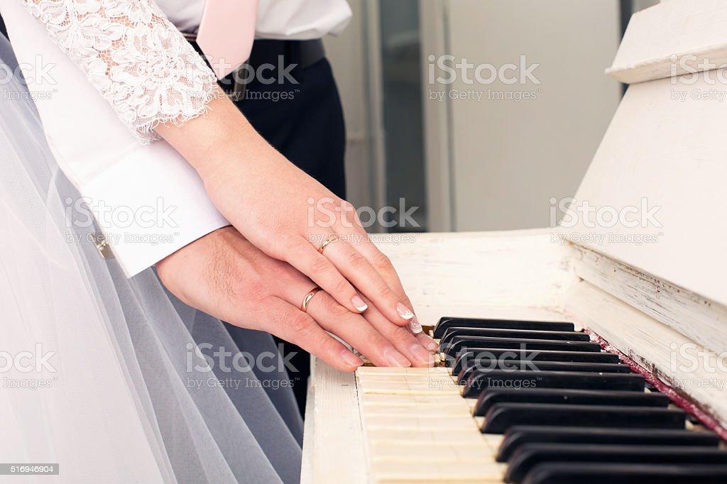 newlyweds play on grand piano keys stock photo