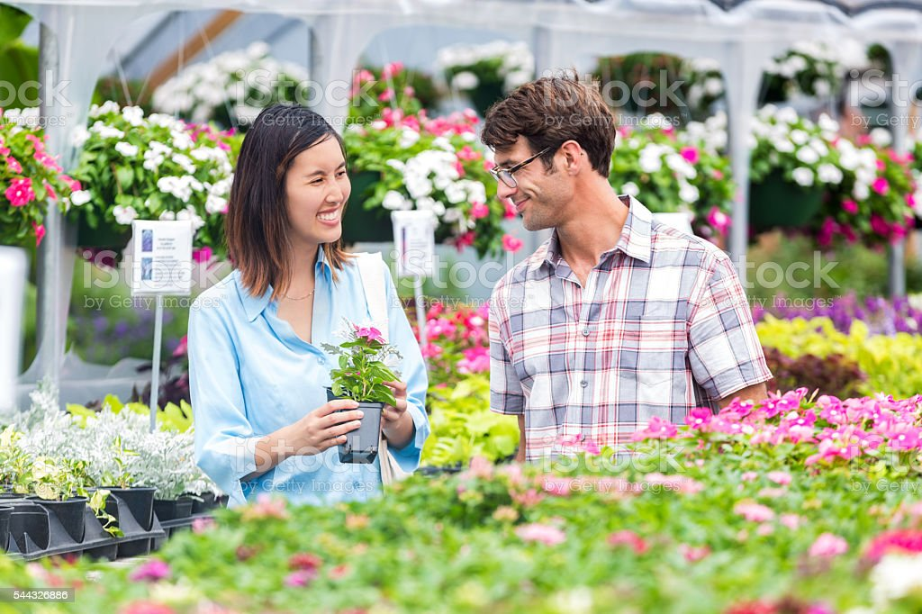 Diverse married couple talk with each other as they shop for flowers...