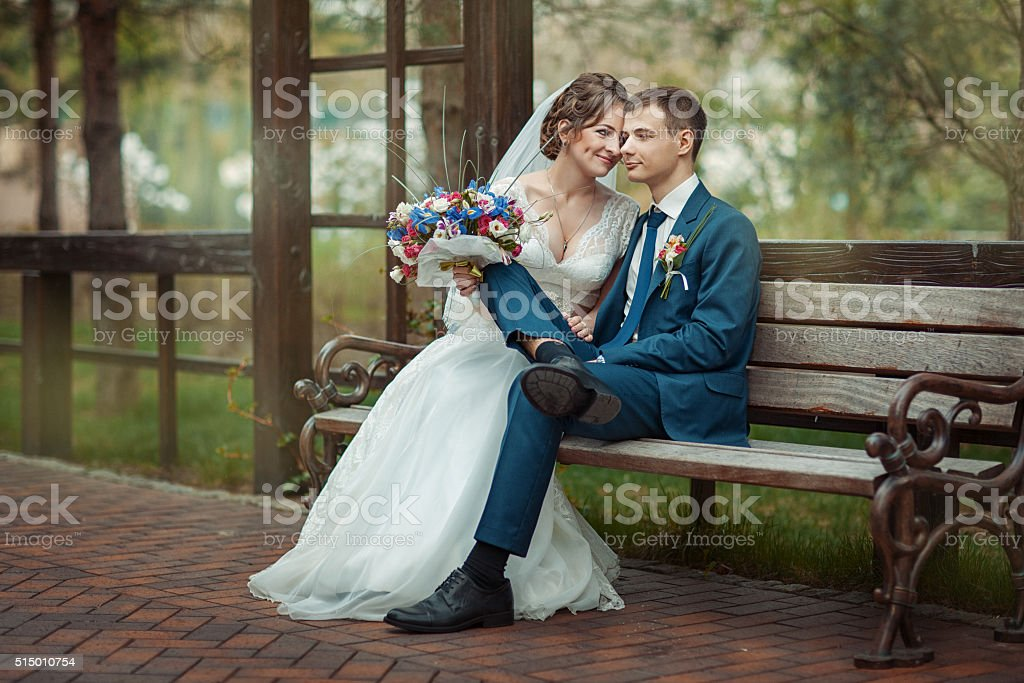 Newlyweds sitting on a bench stock photo