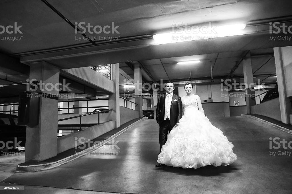 Newlyweds standing in garage bw stock photo
