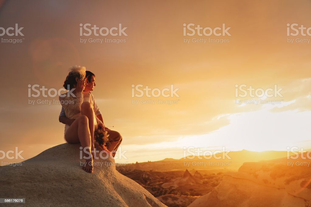 Newlyweds watching romantic sunset stock photo