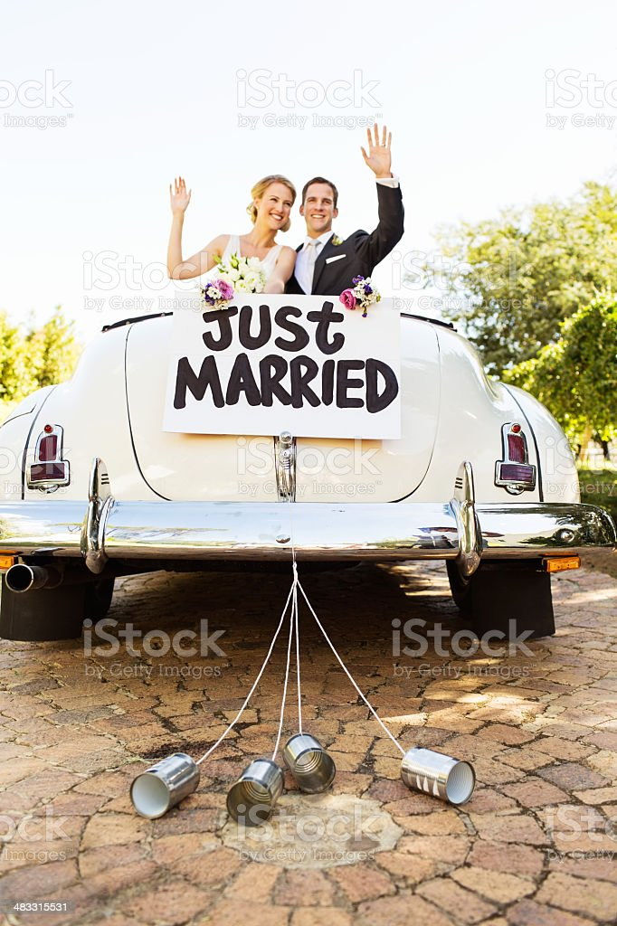 Newlyweds Waving In Convertible Car With Cans Attached To It stock photo