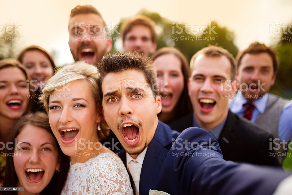 Newlyweds with friends taking selfie stock photo