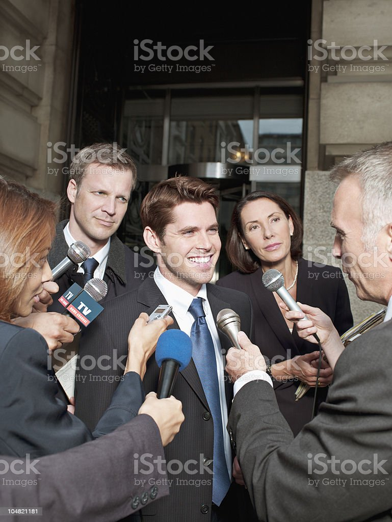 News reporters interviewing smiling man outside courthouse royalty-free stock photo