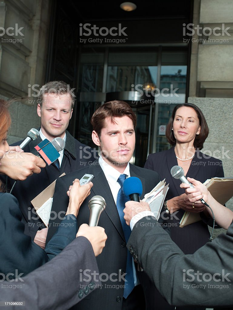 News reporters interviewing smiling man outside courthouse stock photo