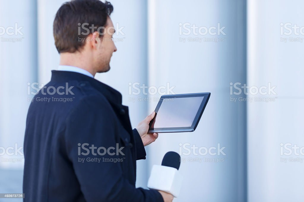 Newshawk is absorbed by information on his tablet stock photo