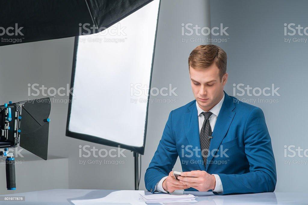 Newsman checking his smartphone stock photo
