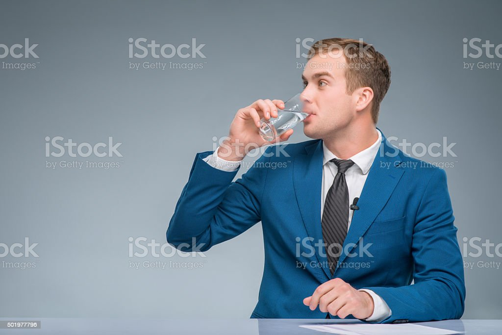 Newsman drinking water at his desk stock photo