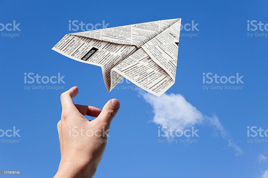 Newspaper airplane flying in the wind stock photo