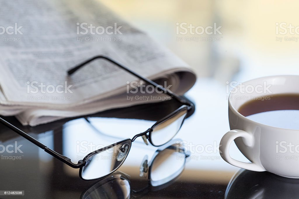 Newspaper and glasses on table stock photo