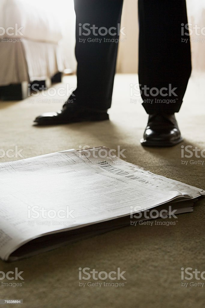 Newspaper and legs of businessman royalty-free stock photo