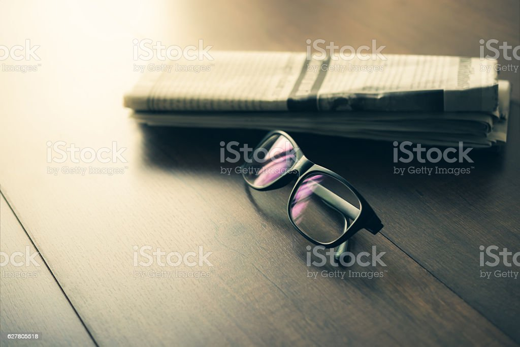 Newspaper and reading glasses on business desk business newspape stock photo