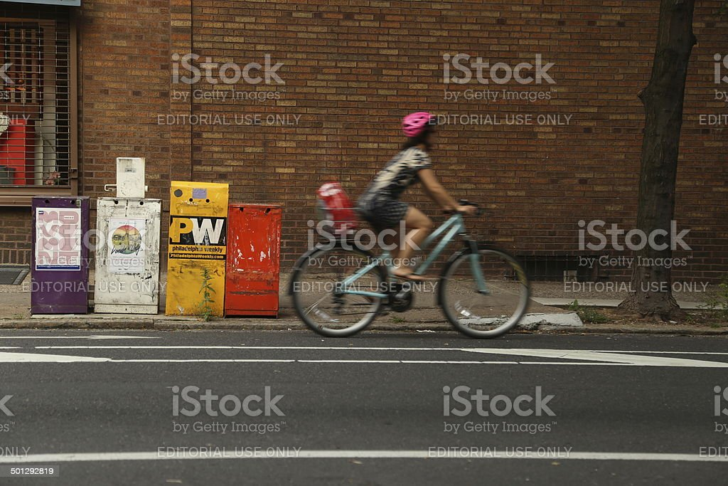 Newspaper box and Bicycle Woman stock photo