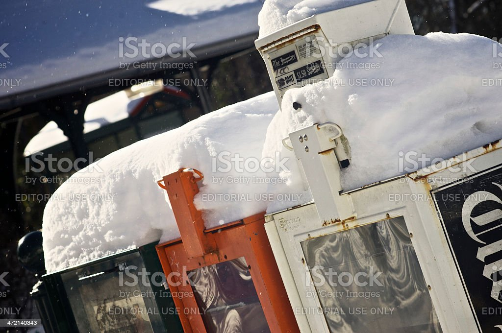 Newspaper boxes covered by snow royalty-free stock photo