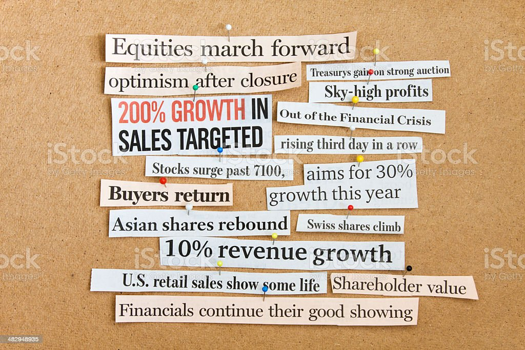 Newspaper headlines on corkboard. Financial optimism is back. stock photo